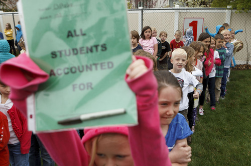 Trent Nelson  |  The Salt Lake Tribune First graders at Granite Elementary stand in the rain after evacuating the school during a statewide earthquake drill Tuesday, April 17, 2012 in Sandy, Utah.