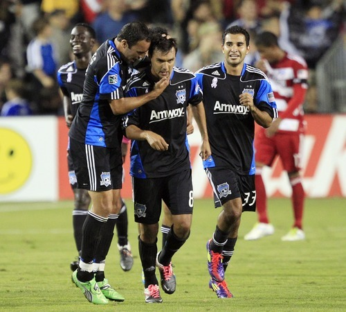 San Jose Earthquakes forward Chris Wondolowski, center, is hugged by teammates Ramiro Corrales, left, and Steven Beitashour after Wondolowski's goal from the penalty spot against FC Dallas during the first half of an MLS soccer game Saturday, Oct. 22, 2011, in Santa Clara, Calif. (AP Photo/Marcio Jose Sanchez)