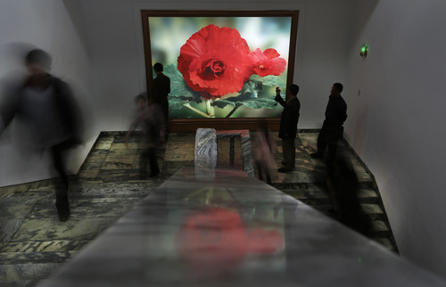 North Koreans walk past a light box featuring a Kimjongilia, a flower named after the late leader Kim Jong Il, during a flower show in Pyongyang, North Korea, Tuesday, April 17, 2012. (AP Photo/Vincent Yu)