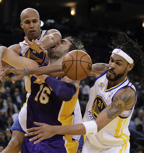 Los Angeles Lakers' Pau Gasol, center, is stripped of the ball by Golden State Warriors' Mikki Moore, right, and Richard Jefferson (44) during the second half of an NBA basketball game Wednesday, April 18, 2012, in Oakland, Calif. (AP Photo/Ben Margot)