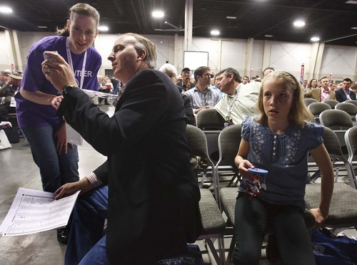 Leah Hogsten  |  The Salt Lake Tribune Delegate Charles Hardy of Sandy with his daughter Abigal, 11, (right)  gets help casting his ballot with fellow delegates electronically with a receiver. The Utah Republican Party held its nominating convention Saturday, April 21 2012, in Sandy at the South Towne Exposition Center.