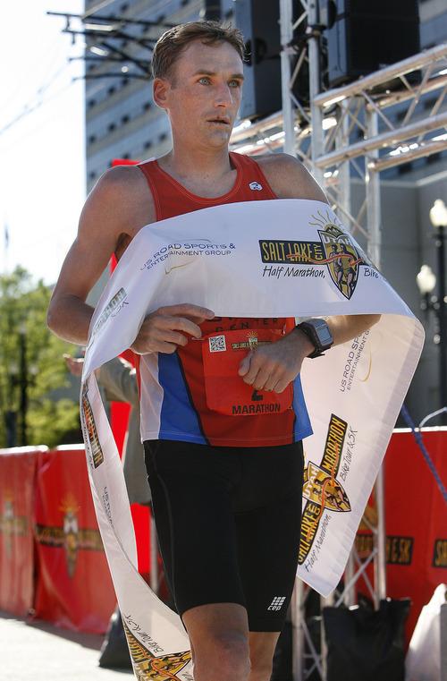 Fritz Van de Kamp crosses the finish line with a time of 2:25.58 to win the Salt Lake City Marathon, Saturday, April 21, 2012.   (AP Photo/The Salt Lake Tribune, Scott Sommerdorf)
