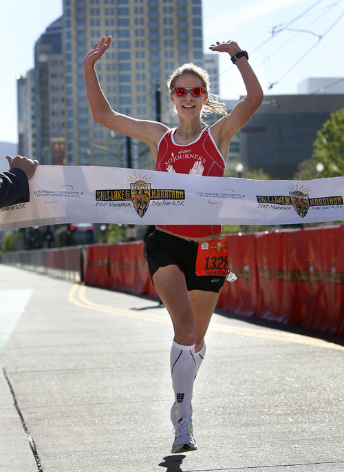 Devra Viercante crosses the finish line in 2:54.56 to be the winning woman runner at the Salt Lake City Marathon, Saturday, April 21, 2012.   (AP Photo/The Salt Lake Tribune, Scott Sommerdorf)