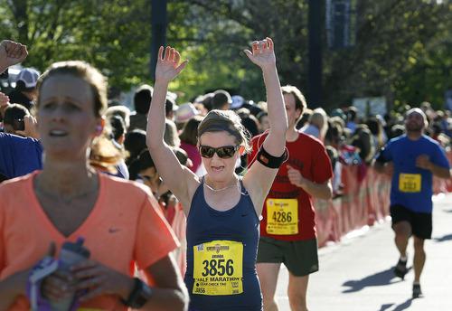 Amanda Phillips of Park City celebrates as she crosses  the finish line in the half marathon at the Salt Lake City Marathon, Saturday, April 21, 2012.   (AP Photo/The Salt Lake Tribune, Scott Sommerdorf)