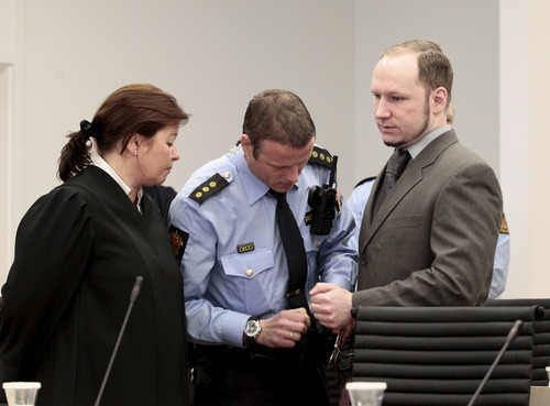 Anders Behring Breivik, right, has his handcuffs removed watched by defence lawyer Vibeke Hein Baera in the courtroom in Oslo Wednesday morning April 25, 2012. After testifying for five days, Anders Behring Breivik listened silently Tuesday as others described the mayhem caused by his bombing of Oslo's government district, a scene one witness described as a