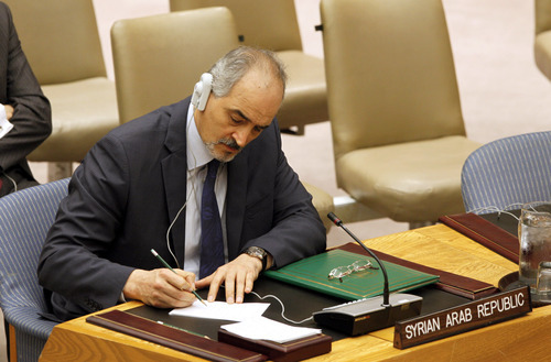 Syrian Ambassador Bashar Jaafari writes during a discussion where members of the Security Council of United Nations voted unanimously to adopt the Syria Observer Mission Resolution, authorizing 300 observers to be sent to Syria, Saturday, April 21, 2012. (AP Photo/David Karp)