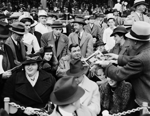 In this September 30, 1936, Works Progress Administration, Federal Writers' Project, photo provided by the New York City Municipal Archives, a man hands a program to baseball legend Babe Ruth, center, as he is joined by his second wife Clare, center left, and singer Kate Smith, front left, in the grandstand during Game 1 of the 1936 World Series at the Polo Grounds in New York. Over 870,000 photos from an archive that exceeds 2.2 million images have been scanned and made available online, for the first time giving a global audience a view of a rich collection that documents New York City life.  (AP Photo/New York City Municipal Archives, WPA Federal Writers' Project)