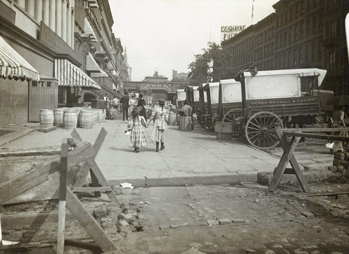 In this circa 1890 photo provided by the New York City Municipal Archives, a pair of girls walk east along 42nd Street in New York. Acker, Merrall and Condit wine shop delivery wagons are on the right and the C.C. Shayne Furrier sign can be seen on the roof overhead. Over 870,000 photos from an archive that exceeds 2.2 million images have been scanned and made available online, for the first time giving a global audience a view of a rich collection that documents life in New York City.  (AP Photo/New York City Municipal Archives, DeGregario Collection (New York Camera Club)