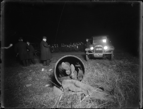 In this 1918 photo provided by the New York City Municipal Archives, police work a homicide after children found the body of Gaspare Candella stuffed in a burlap covered drum out in the middle of a Brooklyn, N.Y. field. Over 870,000 photos from an archive that exceeds 2.2 million images have been scanned and made available online, for the first time giving a global audience a view of a rich collection that documents life and sometimes death in New York City.  (AP Photo/New York City Municipal Archives, NYPD Evidence Collection, Detective Charles A. Carlstrom)