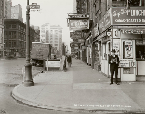In this May 18, 1940 photo provided by the New York City Municipal Archives, a man reads a newspaper on New York's 6th Ave. and 40th St, with the headline: