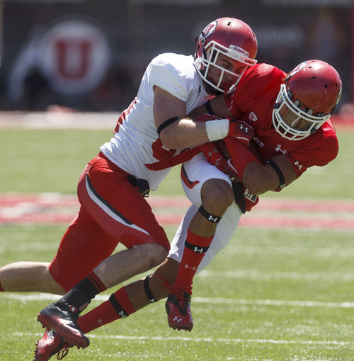 Trent Nelson  |  The Salt Lake Tribune Receiver Dres Anderson is tackled by Tyler Cahoon at the Utah Red and White football game Saturday, April 21, 2012 in Salt Lake City, Utah.