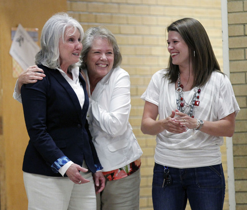 Al Hartmann  |  The Salt Lake Tribune Bountiful Oak Hills Elementary principal Julie Larsen, left, gets a hug from school secretary Debbie Smith and past PTA president Rachel Stevens as she is surprised in a school assembly and awarded a Huntsman award for $10,000.