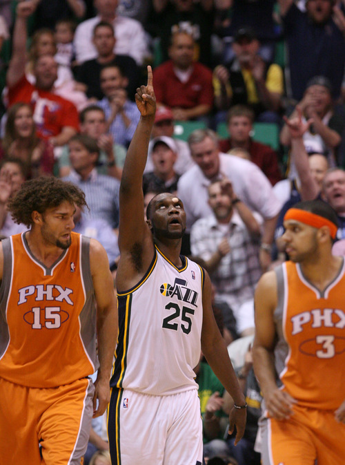 Steve Griffin/The Salt Lake Tribune   With a bandage on his head Utah's Al Jefferson points to the sky Tuesday after making a late basket as he powers the Jazz to a victory over Phoenix and into the playoffs.