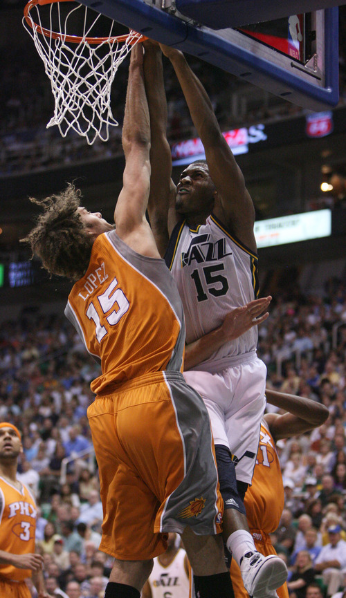 Steve Griffin/The Salt Lake Tribune   Utah's Derrick Favors hammers a dunk over Phoenix center Robin Lopez during a game  at EnergySolutions Arena in Salt Lake City, on Tuesday, April 24, 2012.