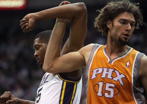 Steve Griffin/The Salt Lake Tribune   Utah's Derrick Favors and Phoenix center Robin Lopez get tangled up during a game  at EnergySolutions Arena in Salt Lake City, on Tuesday, April 24, 2012.