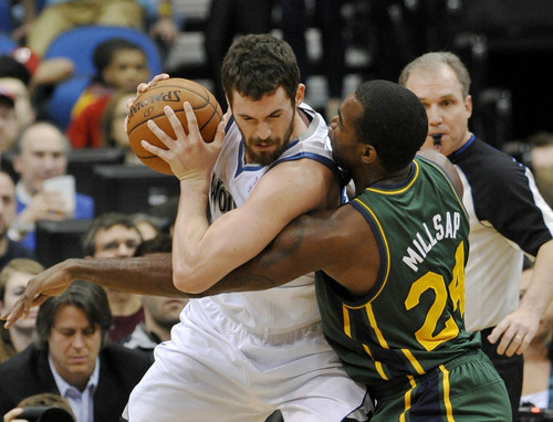 Utah Jazz' Paul Millsap, right, slows up Minnesota Timberwolves' Kevin Love in the first half of an NBA basketball game Wednesday, Feb. 22, 2012, in Minneapolis. (AP Photo/Jim Mone)