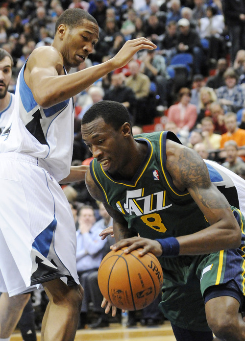 Utah Jazz' Josh Howard, right, drives around Minnesota Timberwolves' Wesley Johnson in the first half of an NBA basketball game Wednesday, Feb. 22, 2012, in Minneapolis. (AP Photo/Jim Mone)