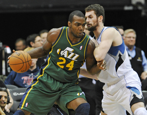 Utah Jazz' Paul Millsap, left, drives around Minnesota Timberwolves' Kevin Love in the second half of an NBA basketball game Wednesday, Feb. 22, 2012, in Minneapolis. The Timberwolves won 100-98. Millsap led the Jazz with 25 points and nine rebounds while Love scored 10 and had 10 rebounds. (AP Photo/Jim Mone)