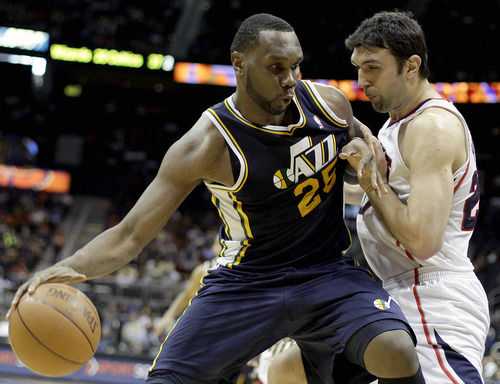 Utah Jazz' Al Jefferson, left, dribbles against Atlanta Hawks center Zaza Pachulia, of Georgia, during the second quarter of an NBA basketball game Sunday, March 25, 2012, in Atlanta. Atlanta won 139-133 Sunday night in the NBA's first quadruple-overtime game since 1997. (AP Photo/David Goldman)