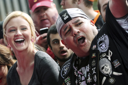 New York Giants fan Jessica Rooney, left, and Oakland Raiders fan Michael Sottile cheer on the players as they arrive on the red carpet for the NFL football draft at Radio City Music Hall, Thursday, April 26, 2012, in New York. (AP Photo/Mary Altaffer)