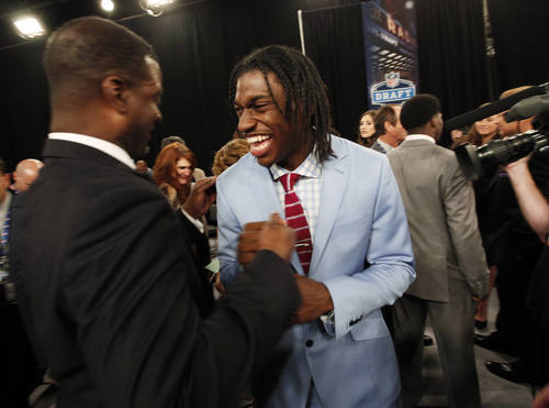 Baylor quarterback Robert Griffin III, center, laughs with another player before the first round of the NFL football draft at Radio City Music Hall, Thursday, April 26, 2012, in New York. (AP Photo/Jason DeCrow)