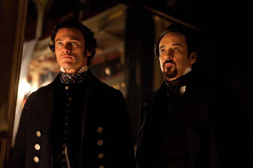 In this film publicity image released by Relativity Media, Luke Evans portrays Detective Fields , left, and John Cusack portrays Edgar Allan Poe in a scene from the gothic thriller