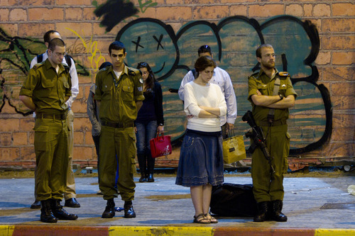 Israeli soldiers and civilians stand to observe a minute of silence as air raid sirens sounds in Tel Aviv to mark Israel's annual Memorial Day for soldiers and civilians killed in more than a century of conflict between Jews and Arabs in Tel Aviv, Israel,Tuesday, April 24, 2012. (AP Photo/Ariel Schalit)