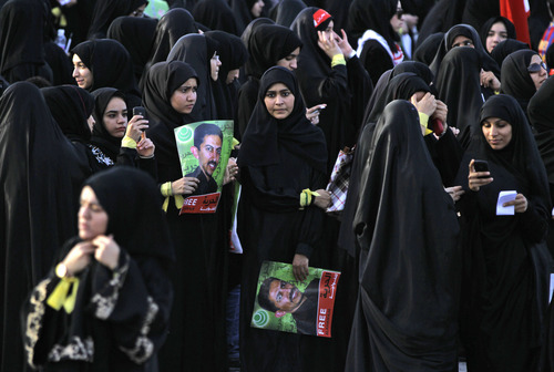Anti-government protesters hold pictures of jailed political leader Abdulhadi al-Khawaja, who has been on a hunger strike for more than 70 days, during a march through Jidhafs, Bahrain, on Tuesday, April 24, 2012. Witnesses said police in Bahrain have used tear gas and water cannons to disperse hundreds of protesters calling for al-Khawaja's release.The Arabic on the pictures reads: