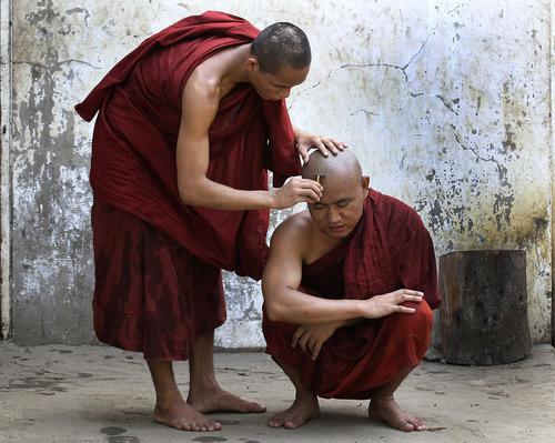 A Myanmar Buddhist monk shaves a fellow monk's head in Yangon, Myanmar Wednesday, April 25, 2012. (AP Photo/Sakchai Lalit)