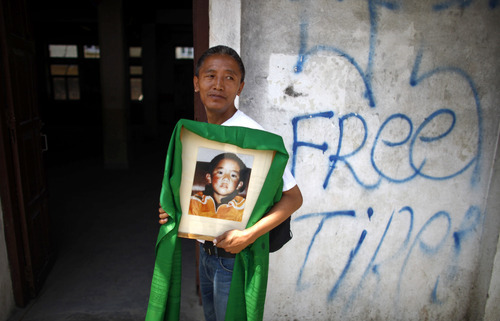 A Tibetan man carries a portrait of Panchen Lama Gendun Choekyi Nyima, the second-highest Tibetan religious leader, on his 23rd birthday in Katmandu, Nepal, Wednesday, April 25, 2012. Nyima was named the reincarnation of the Panchen Lama in 1995 by the Dalai Lama, Tibetan's highest figure who is reviled as a separatist by the Chinese government. He and his family, who are from a remote part of Chinese-controlled Tibet, have not been heard from since and Beijing gave another boy the title. (AP Photo/Niranjan Shrestha)