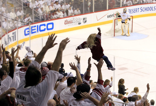 A young Phoenix Coyotes fan is tossed in the air as fans around her cheer on their team as Nashville Predators goalie Pekka Rinne, of Finland, stands in front of the goal during the third period of Game 1 in an NHL hockey Stanley Cup Western Conference semifinal playoff series, Friday, April 27, 2012, in Glendale, Ariz. The Coyotes won 4-3 in overtime. (AP Photo/Ross D. Franklin)