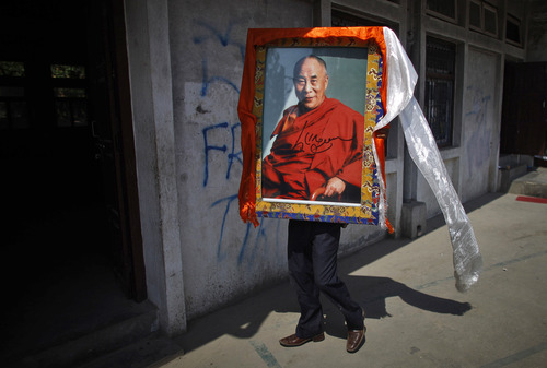 A Tibetan man carries a portrait of Tibetan spiritual leader the Dalai Lama, during a function to mark the 23rd birthday of Panchen Lama Gendun Choekyi Nyima, the second-highest Tibetan religious leader, in Katmandu, Nepal, Wednesday, April 25, 2012. Nyima was named the reincarnation of the Panchen Lama in 1995 by the Dalai Lama, Tibetan's highest figure who is reviled as a separatist by the Chinese government. He and his family, who are from a remote part of Chinese-controlled Tibet, have not been heard from since and Beijing gave another boy the title. (AP Photo/Niranjan Shrestha)