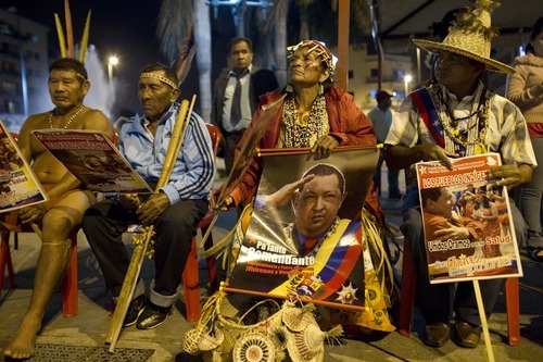 Indigenous people gather for a ritual to pray for the health of Venezuela's President Hugo Chavez in Caracas, Venezuela, Friday, April 27, 2012. Chavez, who returned home Thursday after more than a week of cancer treatment in Cuba, has kept secret some details of his illness, including the type of cancer and the precise location of the tumors. He is seeking re-election in October. (AP Photo/Ariana Cubillos)