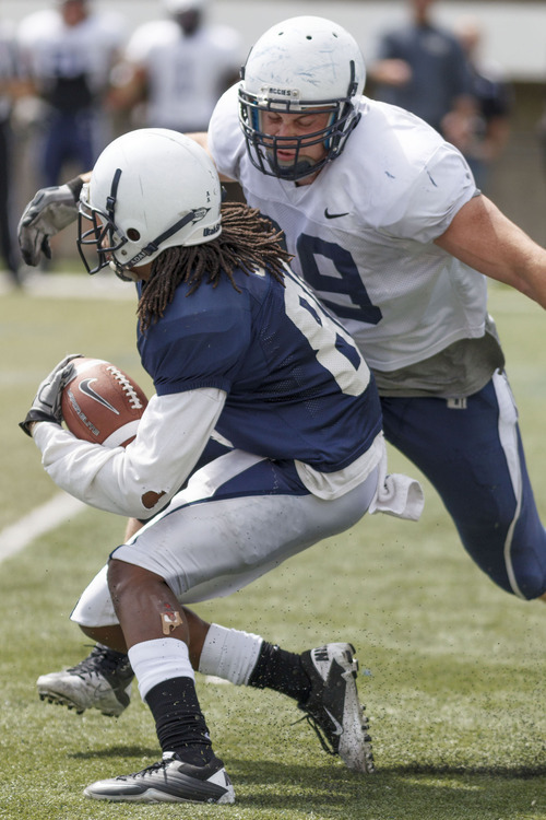Trent Nelson  |  The Salt Lake Tribune Defensive lineman B.J. Larsen moves in to tackle Chuck Jacobs at Utah State's annual Blue and White football game Saturday, April 28, 2012 in Logan, Utah.