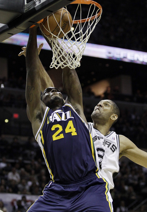 Utah Jazz's Paul Millsap (24) scores as San Antonio Spurs' Tim Duncan, right defends during the second quarter of Game 1 of a first-round NBA basketball playoff series on Sunday, April 29, 2012, in San Antonio. (AP Photo/Eric Gay)