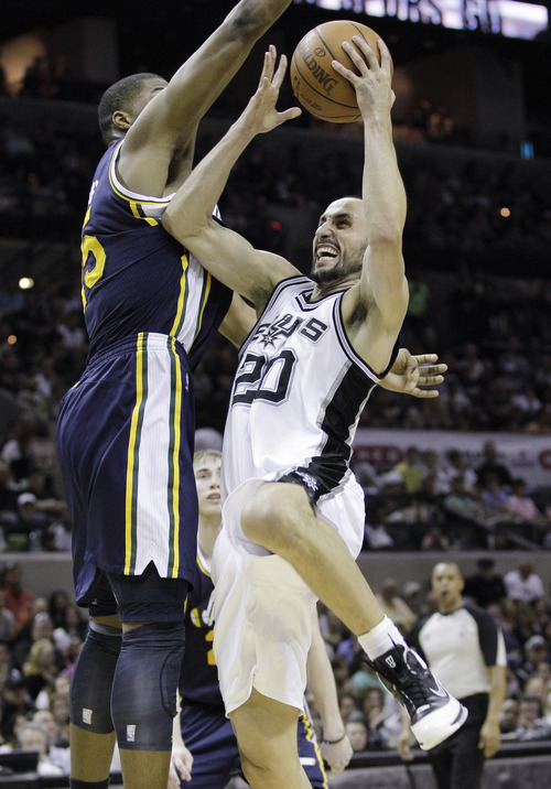 San Antonio Spurs' Manu Ginobili (20), of Argentina, is defended by Utah Jazz's Derrick Favors, left, during the third quarter of Game 1 of a first-round NBA basketball playoff series on Sunday, April 29, 2012, in San Antonio.  San Antonio won 106-91. (AP Photo/Eric Gay)