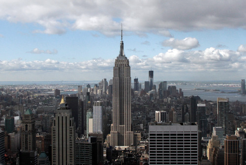 This April 27, 2012, photo shows the Empire State Building, center, and One World Trade Center, rear right, in New York. One World Trade Center, the giant monolith being built to replace the twin towers destroyed in the Sept. 11 attacks, will lay claim to the title of New York City's tallest skyscraper on Monday, April 30, as workers erect steel columns that will make its unfinished skeleton a little over 1,250 feet, just high enough to peak over the observation deck on the Empire State Building. (AP Photo/Richard Drew)