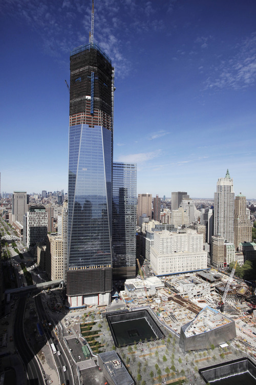 In this April 17, 2012, file photo, One World Trade Center,  rises above the lower Manhattan skyline and the National September 11 Memorial, lower right, in New York. One World Trade Center, the giant monolith being built to replace the twin towers destroyed in the Sept. 11 attacks, will lay claim to the title of New York City's tallest skyscraper on Monday, April 30, as workers erect steel columns that will make its unfinished skeleton a little over 1,250 feet, just high enough to peak over the observation deck on the Empire State Building. The milestone is a preliminary one. The so-called