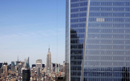 In this April 17, 2012, file photo, One World Trade Center, right, rises above the  Manhattan skyline and the Empire State Building, center, in New York. One World Trade Center, the giant monolith being built to replace the twin towers destroyed in the Sept. 11 attacks, will lay claim to the title of New York City's tallest skyscraper on Monday, April 30 as workers erect steel columns that will make its unfinished skeleton a little over 1,250 feet, just high enough to peak over the observation deck on the Empire State Building, center. The milestone is a preliminary one. The so-called