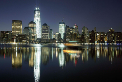 In this March 26, 2012, file photo, One World Trade Center towers above the Lower Manhattan skyline and Hudson River in New York. One World Trade Center, the giant monolith being built to replace the twin towers destroyed in the Sept. 11 attacks, will lay claim to the title of New York City's tallest skyscraper on Monday, April 30 as workers erect steel columns that will make its unfinished skeleton a little over 1,250 feet, just high enough to peak over the observation deck on the Empire State Building. The milestone is a preliminary one. The so-called