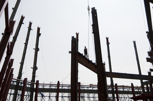 In this March 23, 2012, photo, an ironworker walks a steel beam at the top of One World Trade Center in New York. One World Trade Center, the giant monolith being built to replace the twin towers destroyed in the Sept. 11 attacks, will lay claim to the title of New York City's tallest skyscraper on Monday, April 30, as workers erect steel columns that will make its unfinished skeleton a little over 1,250 feet, just high enough to peak over the observation deck on the Empire State Building. The milestone is a preliminary one. The so-called