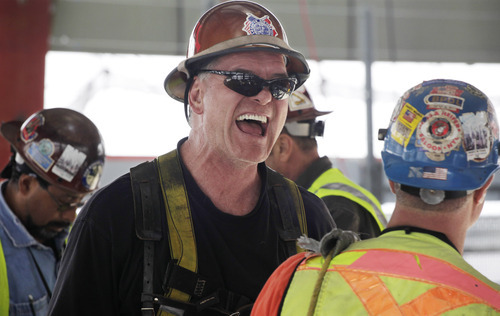 In this March 23, 2012 photo, an ironworker laughs at the end of his shift at the top of One World Trade Center in New York. One World Trade Center, the giant monolith being built to replace the twin towers destroyed in the Sept. 11 attacks, will lay claim to the title of New York City's tallest skyscraper on Monday, April 30, 2012, as workers erect steel columns that will make its unfinished skeleton a little over 1,250 feet, just high enough to peak over the observation deck on the Empire State Building. The milestone is a preliminary one. The so-called