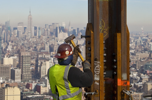 In this Dec. 16, 2010, file photo, an ironworker connects a steel plate to a column at One World Trade Center in New York. The Empire State Building is visible in the rear upper left. One World Trade Center, the giant monolith being built to replace the twin towers destroyed in the Sept. 11 attacks, will lay claim to the title of New York City's tallest skyscraper on Monday, April 30, 2012, as workers erect steel columns that will make its unfinished skeleton a little over 1,250 feet, just high enough to peak over the observation deck on the Empire State Building. The milestone is a preliminary one. The so-called