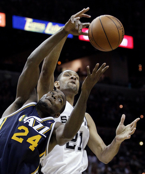 Utah Jazz's Paul Millsap (24) and San Antonio Spurs' Tim Duncan (21) reach for a rebound during the fourth quarter of Game 1 of a first-round NBA basketball playoff series on Sunday, April 29, 2012, in San Antonio. San Antonio won 106-91. (AP Photo/Eric Gay)