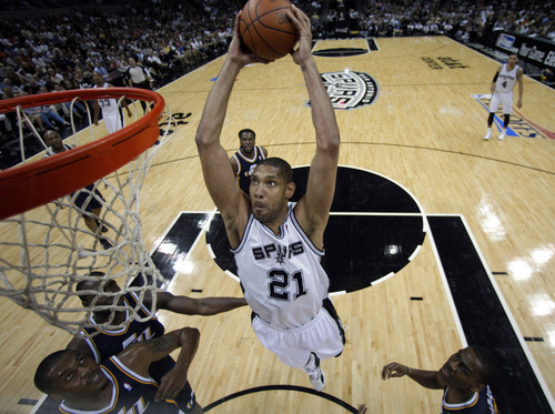 San Antonio Spurs' Tim Duncan (21) drives to the basket over Utah Jazz defenders during the first half of Game 1 of a first-round NBA basketball playoff series on Sunday, April 29, 2012, in San Antonio.  San Antonio won 106-91.(AP Photo/Eric Gay)