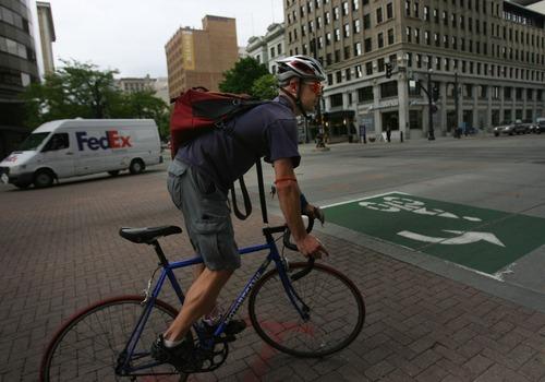 Kim Raff | The Salt Lake Tribune A J.J. Merrill rides a bicycle down 200 South in downtown Salt Lake City, Utah on April 30, 2012.