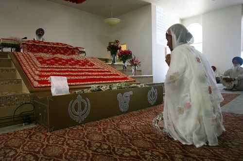 Kim Raff | The Salt Lake Tribune Gurmail Kaur pays respect to the Guru Granth Sahib, the Sikh holy book, during the Sikhs of Utah worship service at the Sikh Temple in Taylorsville on April 22, 2012.