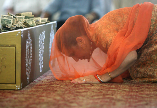 Kim Raff | The Salt Lake Tribune Surinder Gill pays respect to the Guru Granth Sahib, the Sikh holy book, during the Sikhs of Utah worship service at the Sikh Temple in Salt Lake City, Utah on April 22, 2012.