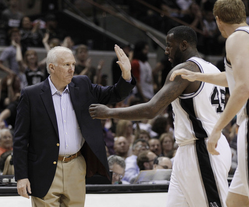 San Antonio Spurs coach Gregg Popovich, left, greets his players during a timeout in the fourth quarter of an NBA basketball game against the Portland Trail Blazers, Monday, April 23, 2012, in San Antonio. San Antonio won 124-89, clinching the top seed in the Western Conference. (AP Photo/Eric Gay)