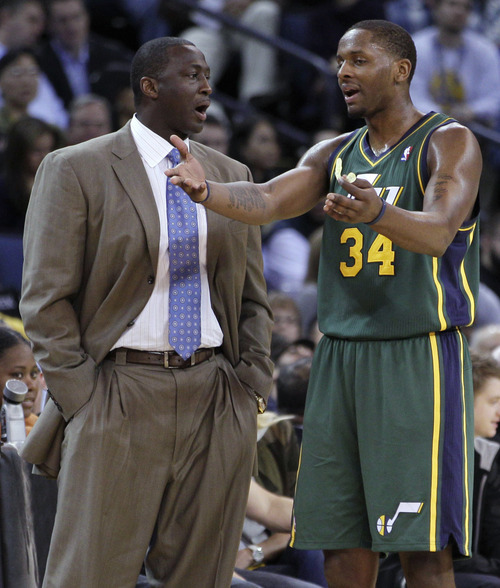 Utah Jazz coach Tyrone Corbin, left, speaks with C.J. Miles during the first half of an NBA basketball game against the Golden State Warriors on Thursday, Feb. 2, 2012, in Oakland, Calif. (AP Photo/Ben Margot)